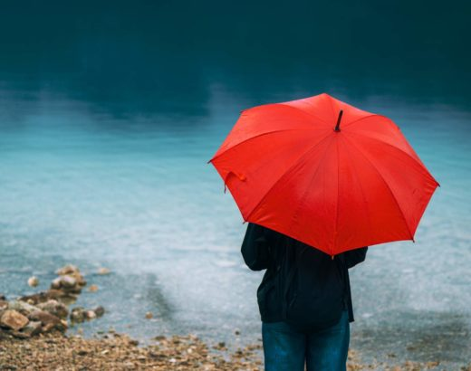 woman standing under red umbrella and pondering love and hurt