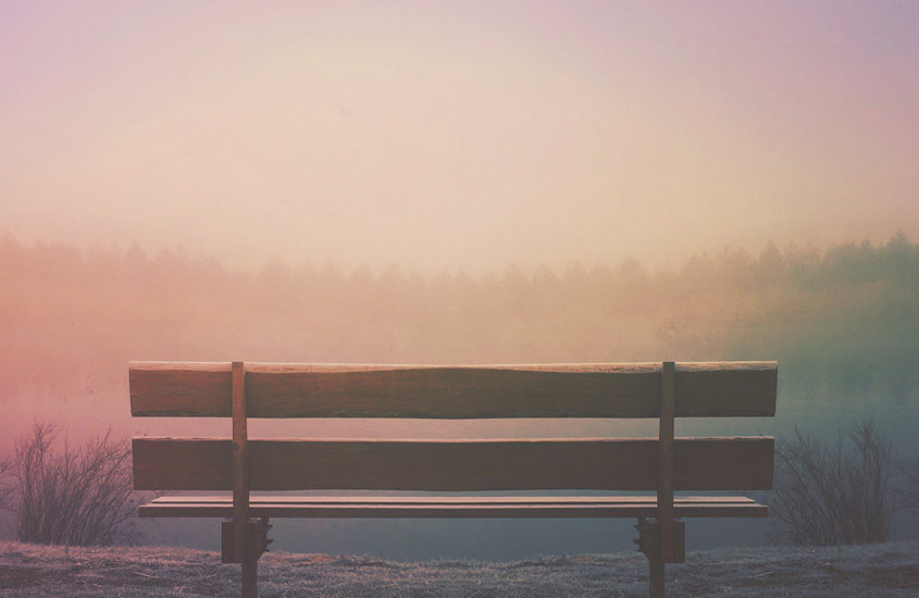 wooden bench facing sunset
