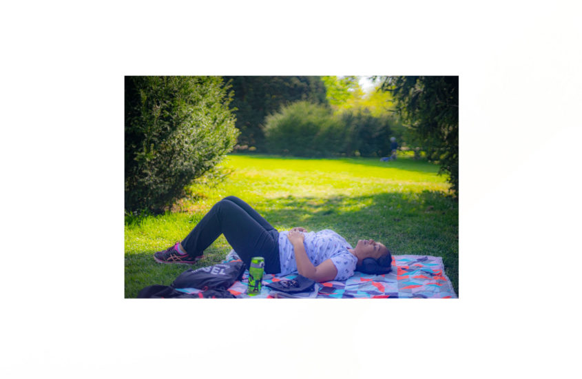 lying on a cloth on the grass in the park